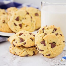 a few cake mix chocolate chip cookies on the counter next to a glass of milk with a plate full in the background.