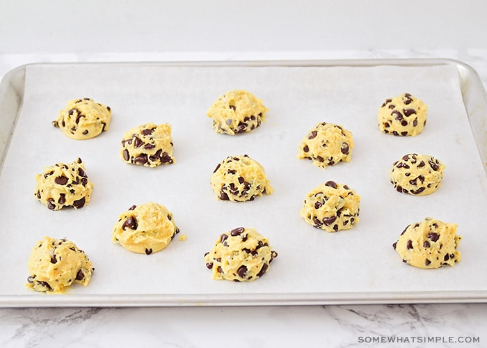 balls of chocolate chip cookie dough layed out on a baking sheet lined with parchment paper