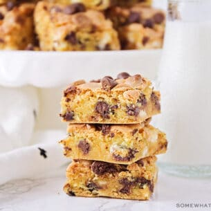 a stack of chocolate chip cookie bar squares made from cake mix next to a jar of milk with a cake stand filled with more bars behind it.