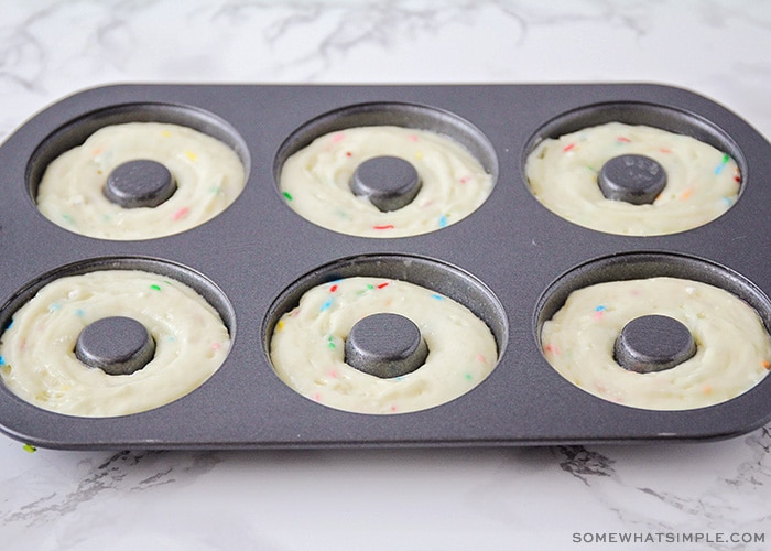 a donut pan with each slot filled with cake mix batter