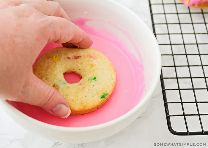 a hand dipping a donut into pink icing