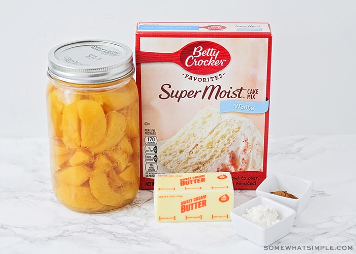 a jar of fresh peaches, a box of white Betty Crocker cake mix, a stick of butter and some cinnamon and flour on the counter