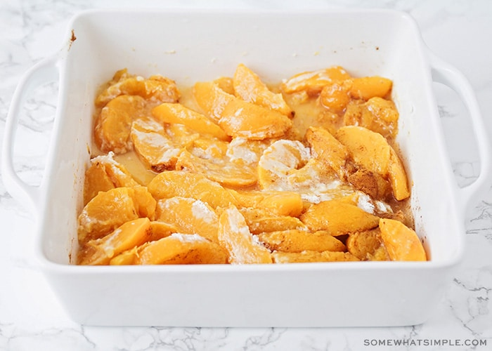 slices of peaches in a baking dish that have been tossed in flour