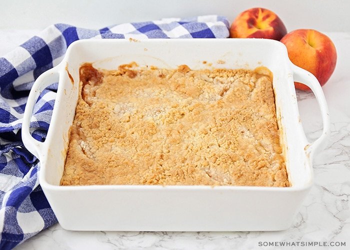 a cake mix peach cobbler that is fresh out of the oven and is golden brown on top