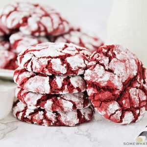 a stack of red velvet cake mix cookies with a dusting of powdered sugar next to a glass jar of milk. Behind these are another plate full of more cookies.