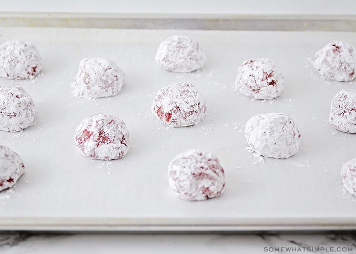 ball of cookie dough covered in powdered sugar on a baking sheet lined with parchment paper