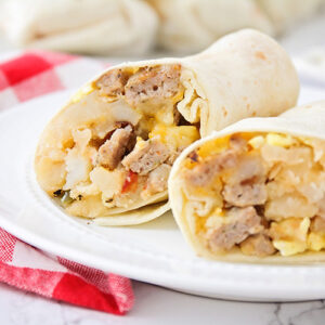 a breakfast burrito filled with potatoes, eggs, sausage and cheese that has been cut in half and is sitting on a white plate