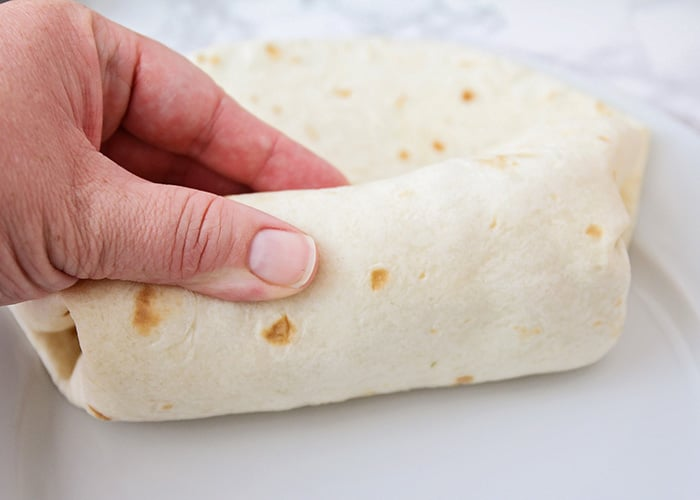 a hand holding a breakfast burrito that is being rolled up