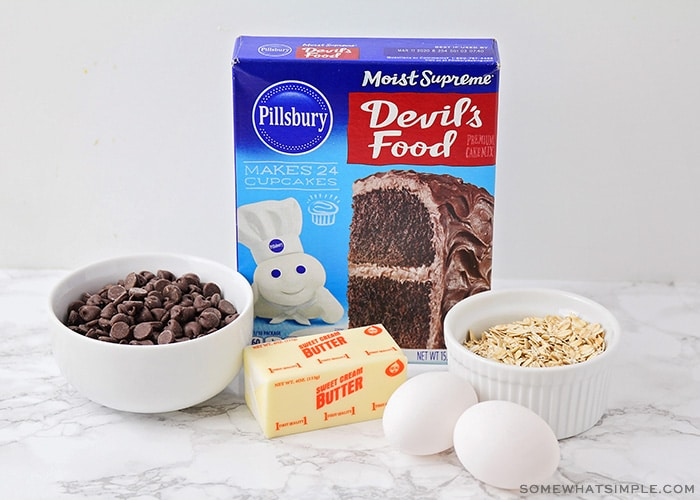 a box of Pillsbury Devil's Food cake mix, a bowl of chocolate chips, a stick of butter, two eggs and a small bowl of oats on a counter