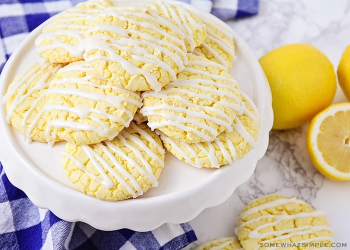 a stack of lemon cookies made from a box of cake mix with white frosting drizzled over the op