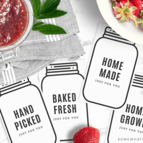 several mason jar gift tags cut out and laid on the counter next to fresh strawberries and a jar of strawberry jam