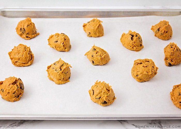 balls of pumpkin cookie dough with chocolate chips on a parchment lined cookie sheet