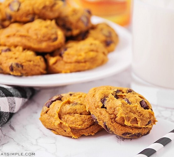 two pumpkin cake mix chocolate chip cookies on a counter next to a glass of milk and a plate of cookies in the background