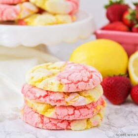 a stack of strawberry lemonade cookies on a counter next to strawberries and lemons