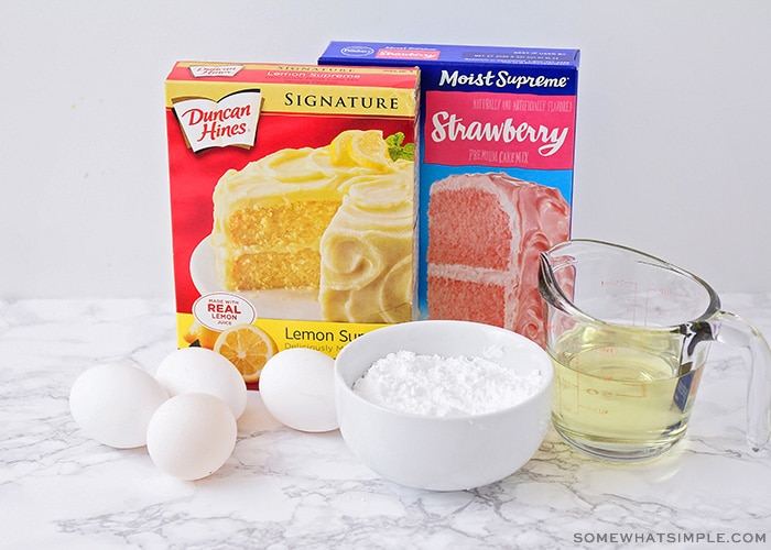 a box of duncan hines lemon cake mix, a box of pillsbury strawberry cake mix, eggs, a bowl of powdered sugar and oil on a counter