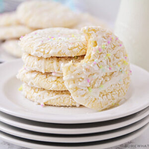 a stack on white cake mix cookies on a plate topped with a white glaze drizzled on top and pastel colored sprinkles