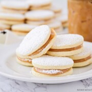 a plate of homemade alfajores with powdered sugar on a table made using this easy recipe with a jar of dulce de leche behind it