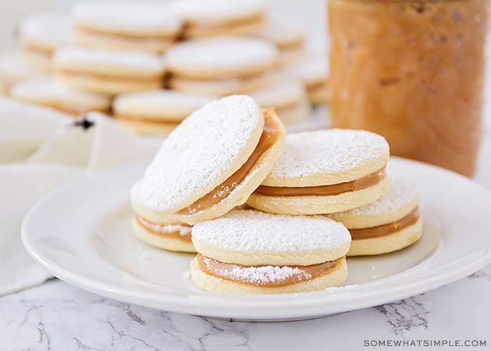 a plate of homemade alfajores with powdered sugar on a table made using this easy recipe