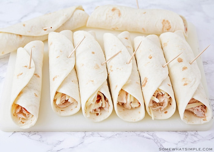 several flour tortillas rolled up that have shredded chicken sticking out and each one has a toothpick stuck in it to keep them from unrolling.