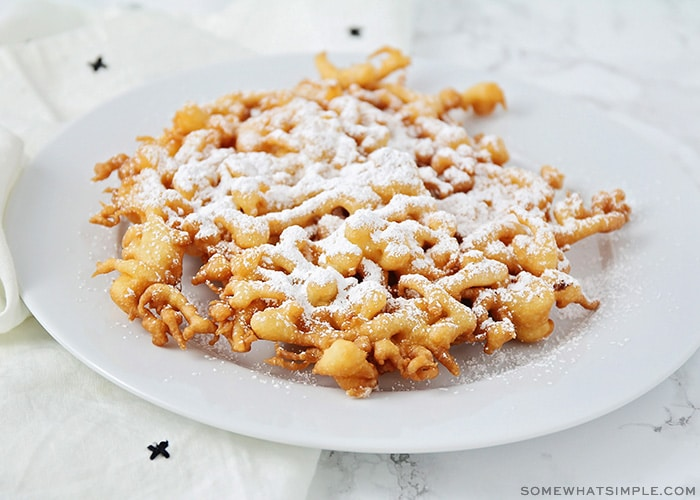 a freshly cooked funnel cake on a plate topped with powdered sugar