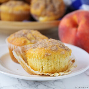 two peach muffins on a white plate with a streusel topping