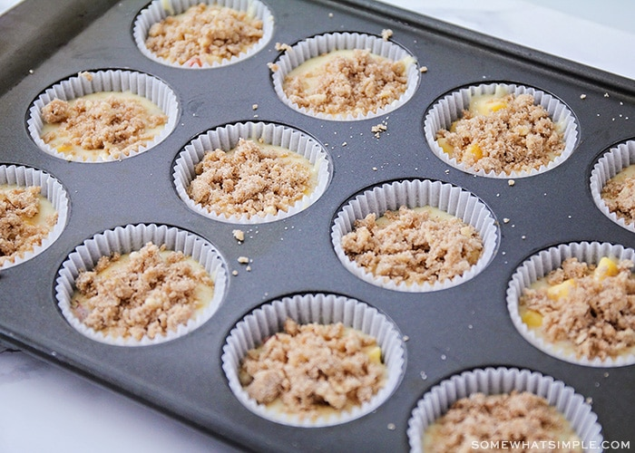 uncooked batter in a muffin tin topped with cinnamon and sugar