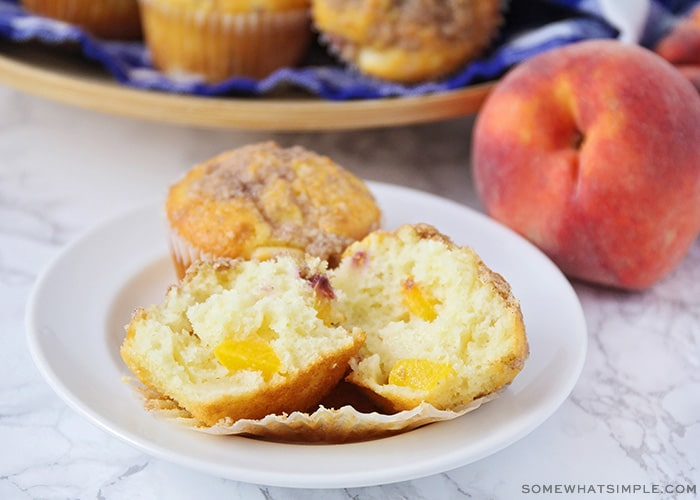 a freshly baked muffin with peach chunks inside and topped with a streusel topping