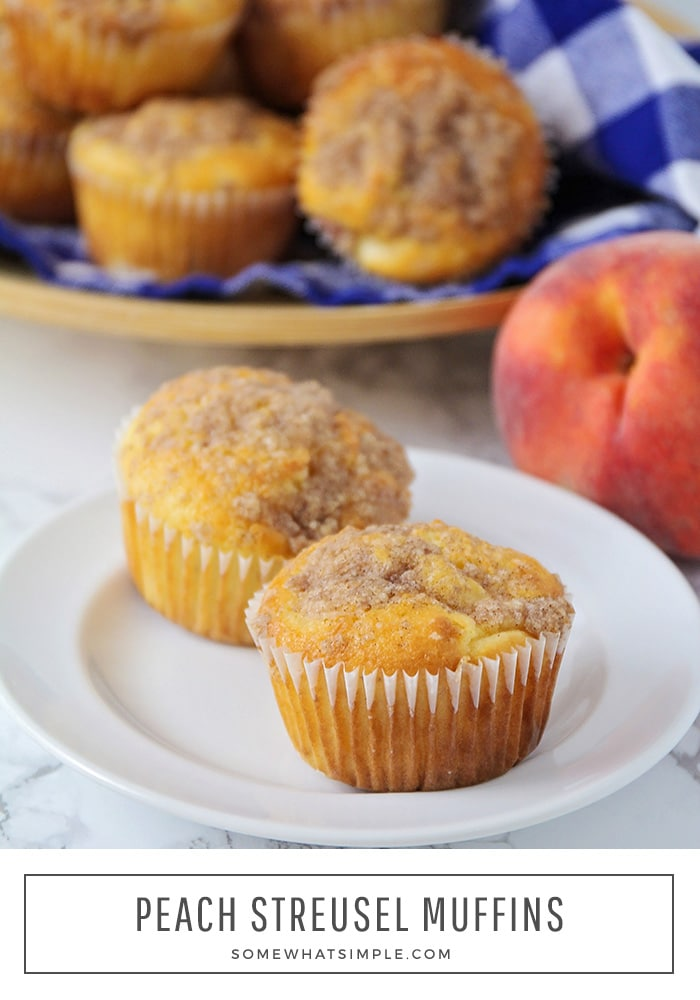 a close up of two peach streusel muffins on a white plate