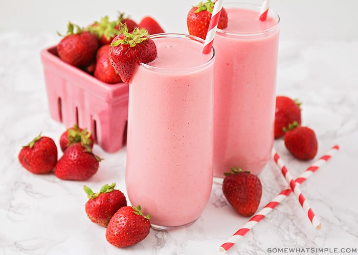 two tall glasses of a strawberry Julius with a whole strawberry sitting on the rim of the glass