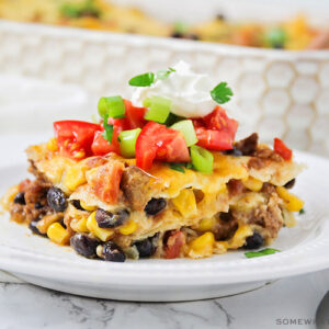 a square of taco casserole filled with ground beef, cheese, beans and corn and topped with diced tomatoes and green onions with a dollop of sour cream