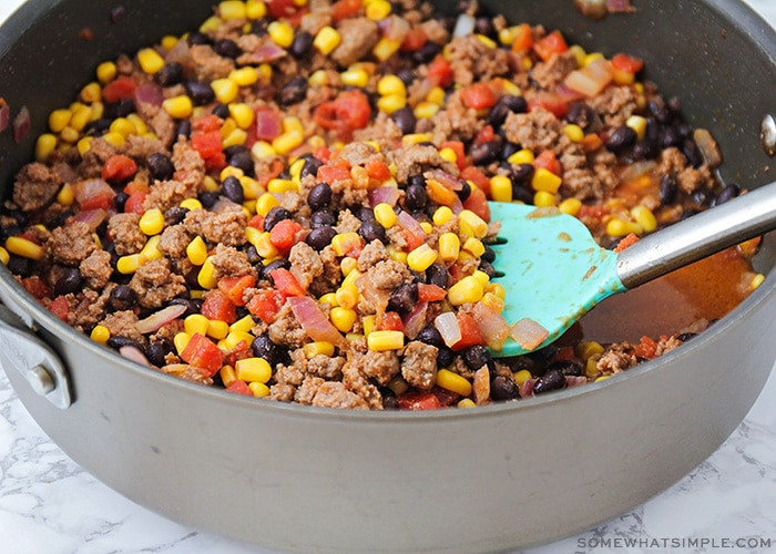 a skillet filled with ground beef, corn, black beans and tomatoes