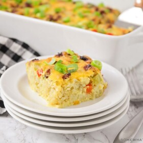 a square of tater tot breakfast casserole with pieces of bell peppers and sausage on a stack on white plates