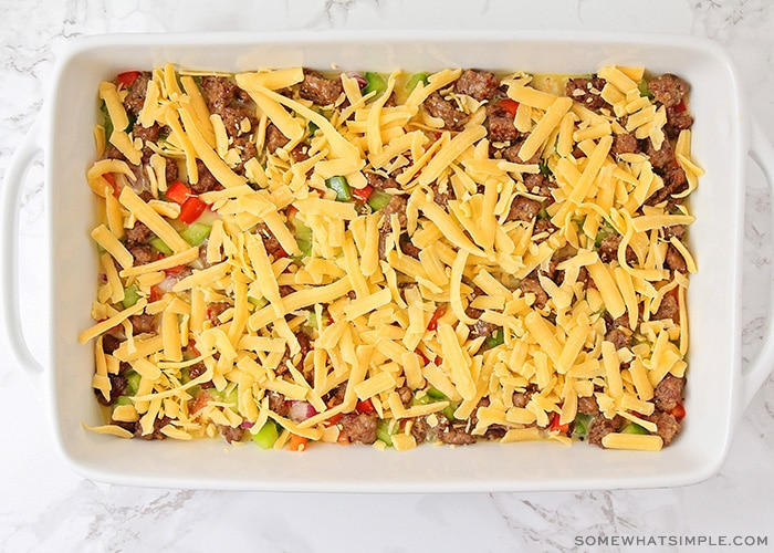 an uncooked tater tot casserole topped with shredded cheese
