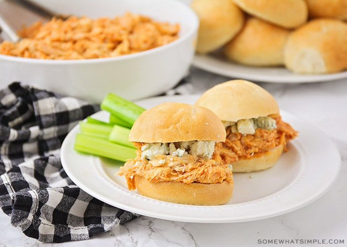 two buffalo chicken sliders on a plate with celery sticks