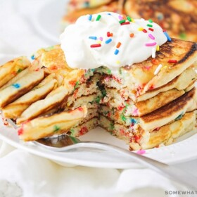 a stack of cake mix pancakes topped with whipped cream and sprinkles