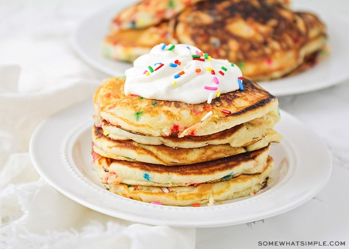 fluffy pancakes topped with whipped cream and sprinkles