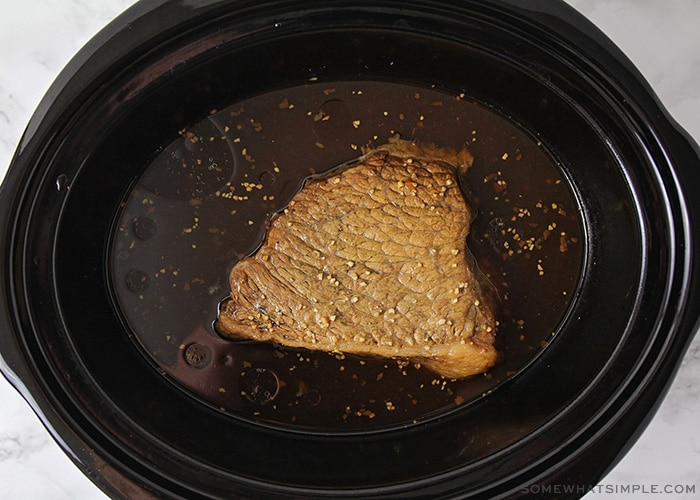 a cooked pot roast in a slow cooker