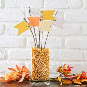 a fall centerpiece made with pennants and twigs on a table
