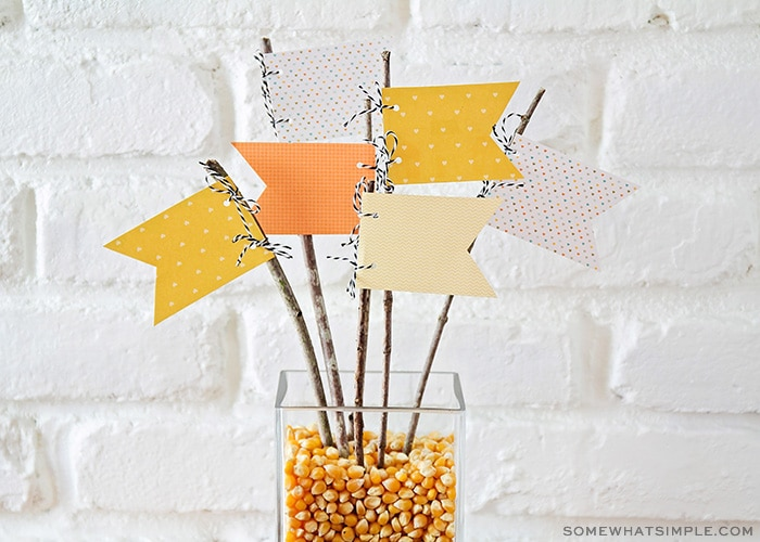 fall centerpiece with popcorn kernels and paper pennants
