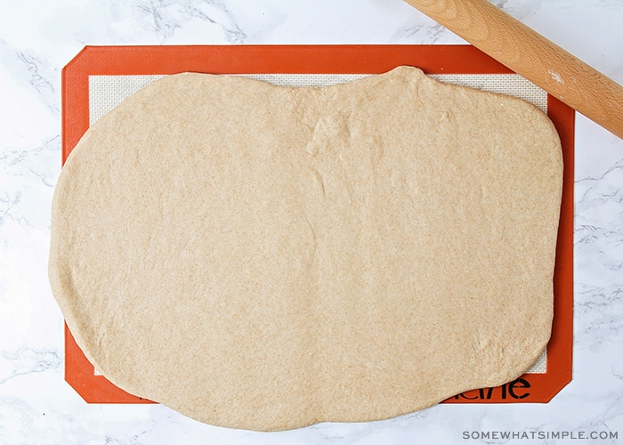 wheat bread dough rolled out on a baking mat
