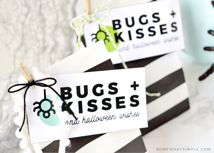 two halloween treat bags with a bugs and kisses tag attached to each one