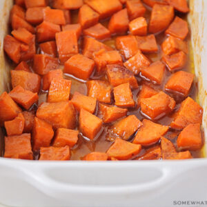 a baking pan filled with candied yams in a brown sugar glaze