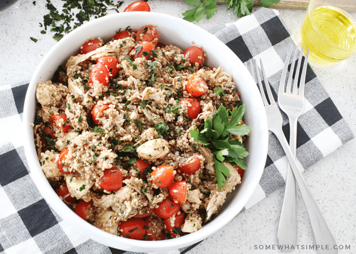a bowl filled with Caprese quinoa chicken salad that's been tossed