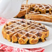 cinnamon syrup being poured over gingerbread waffles