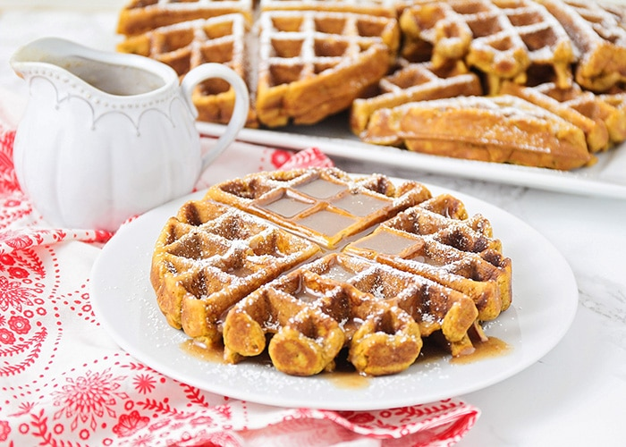a gingerbread waffle dusted with powdered sugar and topped with syrup