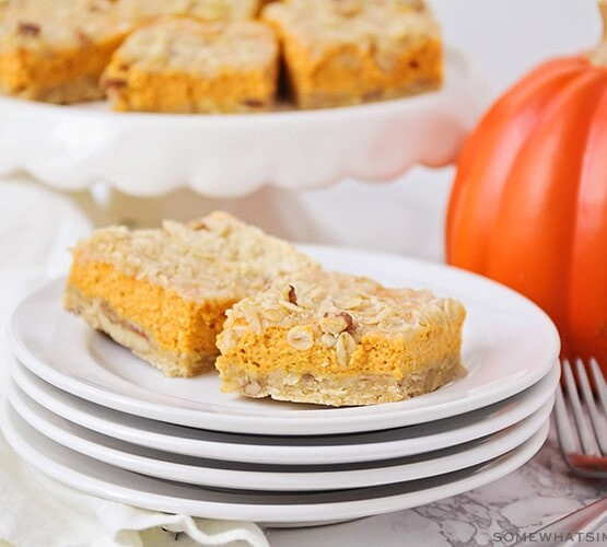 two squares of pumpkin pie bars on a stack of plates