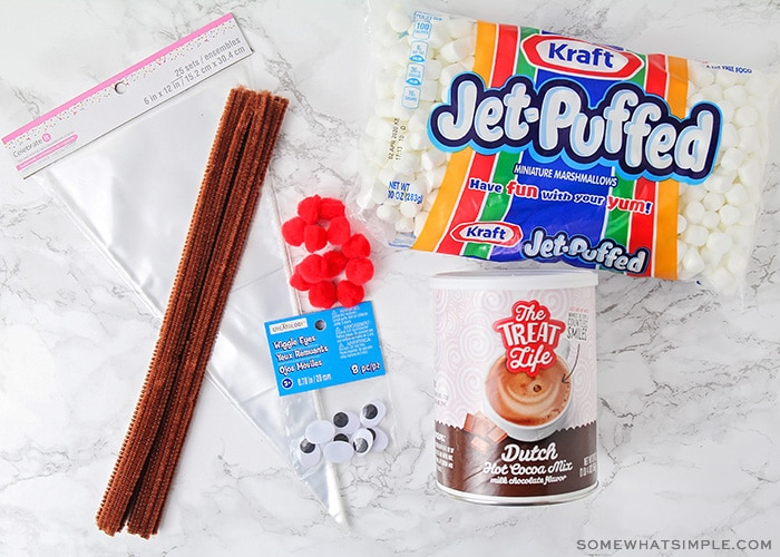 marshmallows, pipe cleaners, hot chocolate, plastic bags an googly eyes on a counter