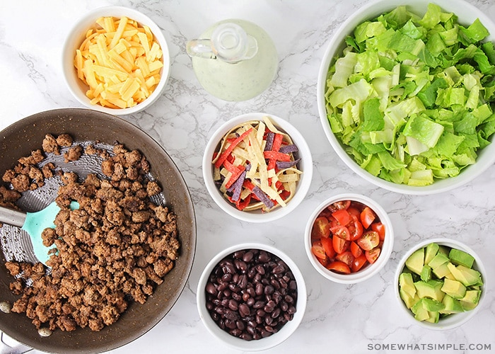 looking down on small bowls filled with taco salad ingredients