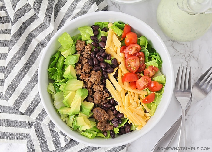looking down on a salad topped with avocado, ground beef, cheese, beans and tomatoes