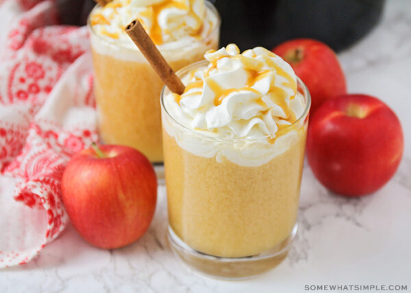 a glass of apple cider topped with whipped cream and caramel